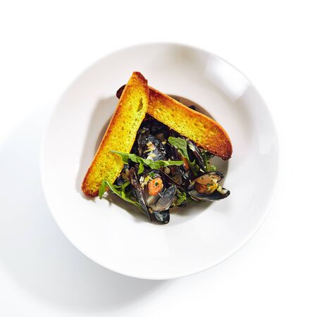 Top view of blue mussels in cream sauce with spicy french baguette on white restaurant plate isolated. Delicious seafood dish with prepared seashells or mytilus, fresh greens and arugula side view