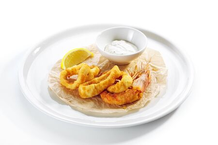 Breaded fried squid rings and shrimp with tartar sauce on white restaurant plate isolated. Roasted seafood fast food with lemon and deep fried onion ring on kraft paper side view Reklamní fotografie