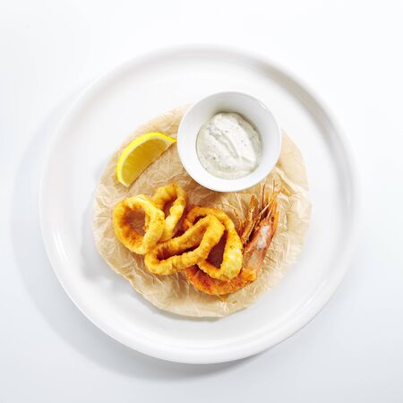 Breaded fried squid rings and shrimp with tartar sauce on white restaurant plate isolated. Roasted seafood fast food with lemon and deep fried onion ring on kraft paper top view
