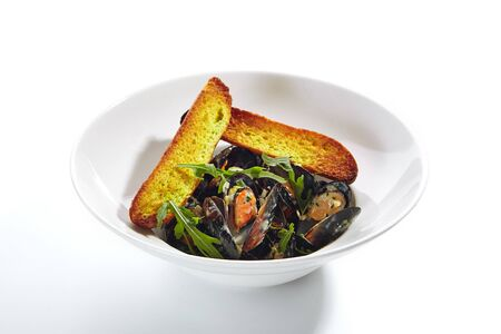 Macro shot of blue mussels in cream sauce with spicy french baguette on white restaurant plate isolated. Delicious seafood dish with prepared seashells or mytilus, fresh greens and arugula close up