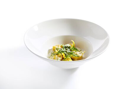 Tortellini with cep mushrooms and pesto sauce on white restaurant plate isolated. Macro shot of homemade yellow Italian ravioli pasta with boletus, arugula and vegetable filling closeup