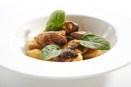 Roasted boletus or porcini mushrooms with baked potatoes and fresh spinach greens on white restaurant plate isolated. Fried delicious ceps, porcino or penny bun healthy dining closeup 版權商用圖片