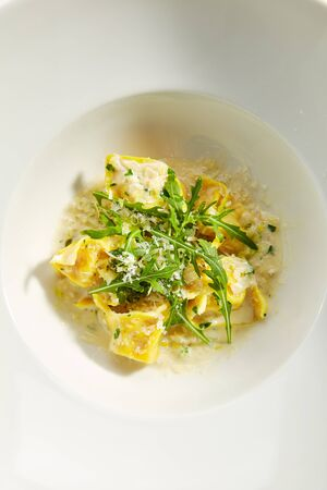Tortellini with cep mushrooms and pesto sauce on white restaurant plate isolated. Top view of homemade yellow Italian ravioli pasta with boletus, arugula and vegetable filling