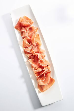 Sliced jamon iberico, prosciutto or speck on white restaurant plate isolated. Spanish traditional delicacy with dry cured ham, raw pork tapas topview