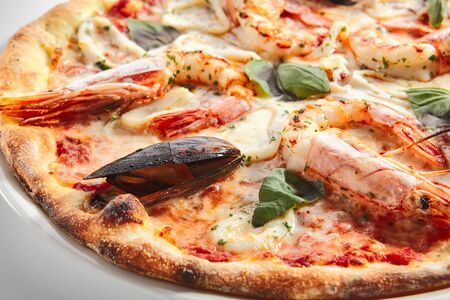 Italian seafood pizza with squid rings, mussels and shrimps on white restaurant plate isolated. Pizza ai frutti di mare topped with tomato sauce, basil and mozzarella closeup