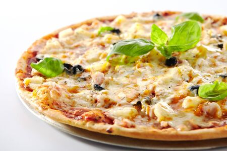 Thin Hawaiian pizza with chicken fillet, pineapples and olives on restaurant plate isolated. Delicious ham and pineapple alternative pizza with meat, bacon, fresh basil and mozzarella cheese closeup