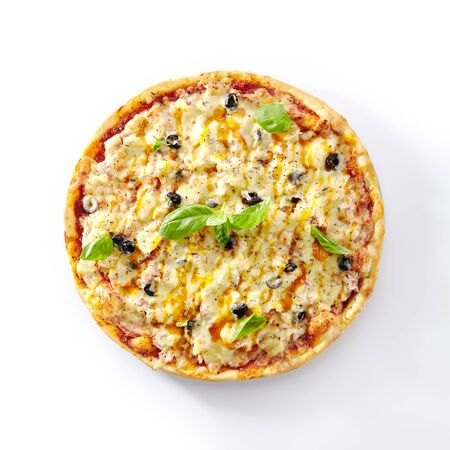 Thin Hawaiian pizza with chicken fillet, pineapples and olives on restaurant plate isolated. Delicious ham and pineapple alternative pizza with meat, bacon, fresh basil and mozzarella cheese top view Stock Photo