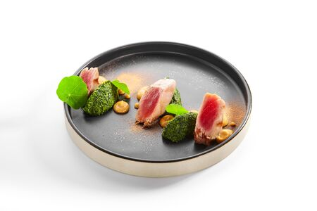Tuna fillet with stewed spinach side view. Delicious seafood with spices and greenery on plate. Tasty cooked meal with fish and sauce. Haute cuisine, food presentation. Traditional recipe