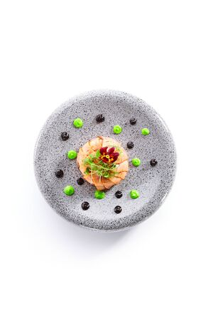 Salmon olivier salad with sauces. Sliced fish dish with greenery. Tasty seafood decorated with violet flower. Haute cuisine on plate. Restaurant meal, elegant food composition Reklamní fotografie