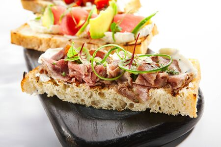 Bruschetta with pastrami closeup view. Italian snack with meat and greenery. Baked baguette with beef. Traditional antipasto, delicious starter dish. Food composition, culinary presentation