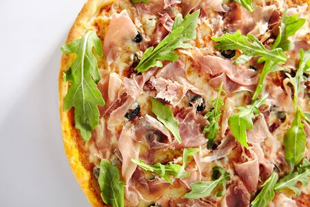 Traditional italian pizza with dried tomatoes, capers, prosciutto, arugula and mozzarella cheese isolated. Delicious italy flatbread with thin slices of ham cutout, hot tasty fast food top view