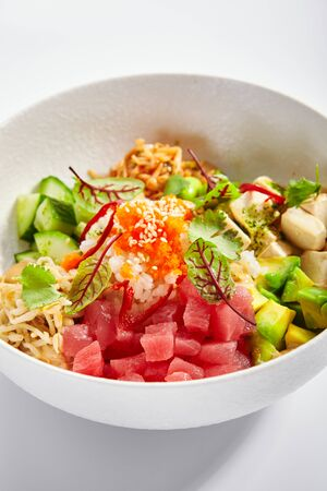 Poke with tuna and noodles. Hawaiian salad with avocado and tofu closeup view. Traditional polynesian dish with rice and cheese. Delicious native cuisine. Meal served with edamame, vegetables and soybean
