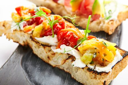 Delicious bruschetta with baked peppers closeup view. Tasty roasted bread with cheese and vegetables. Traditional italian antipasto with greenery on wooden tray. European cuisine, food composition
