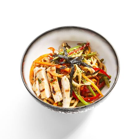 Wok udon with vegetables and chicken side view. Traditional asian meal on white table. Delicious dish with sliced meat, carrot and pepper. Tasty noodles with seasonings. Food composition
