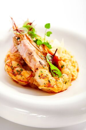 Risotto tom yam with argentinian shrimp. Delicious thai dish with seafood closeup view. Traditional asian meal with rice and aromatic greenery. Food composition on white plate. Restaurant delicacy