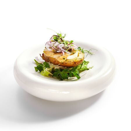 Baked potato with egg and pickled onion. Aromatic dish with green parsley closeup view. Cut vegetables with sauce on white plate. Restaurant food composition, culinary presentation