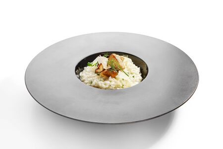 Porcini risotto side view. Tasty rice with white mushrooms. Traditional italian food. Delicious meal with fresh greenery. Restaurant dish, served culinary composition. European recipe