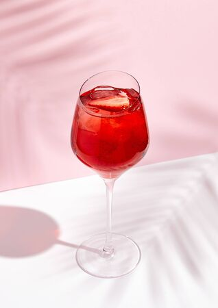 Red summer cocktail in wine glass on creative background. Shadows of palm leaf on pink wall and white floor.