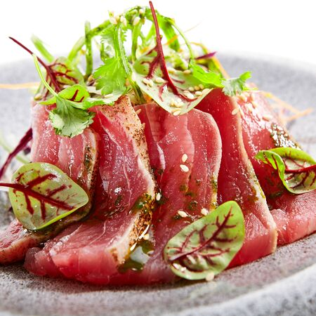 Tataki tuna closeup view. Traditional japanese culinary method. Delicious fish on plate. Tasty sliced seafood with greenery and seasonings. Asian cuisine, food composition. Restaurant dish Reklamní fotografie