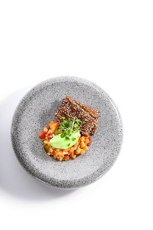 Salmon tartare top view. Raw red fish with seasoning and crackers in plate. Served chopped fresh tuna with bread slices. Seafood restaurant food with herbs decoration. Marine delicacy, gourmet meal