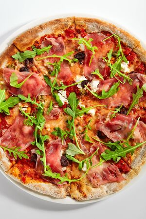 Pizza with parma ham and artichoke. Delicious italian meal with prosciutto. Traditional baked dish decorated with aromatic arugula and meat. Traditional european recipe, culinary presentation
