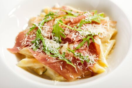 Penne in parmesan sauce. Served traditional Italian cuisine. Pasta with prosciutto, truffle oil and arugula leaves in plate. Italy culinary. Restaurant food portion, main course close up