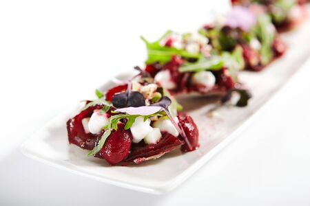 Beetroot tartare with goat cheese on tray. Delicious snacks with arugula and spices. Haute cuisine. Restaurant vegetable apperizers served with fresh greenery. Food presentation, culinary recipe Reklamní fotografie