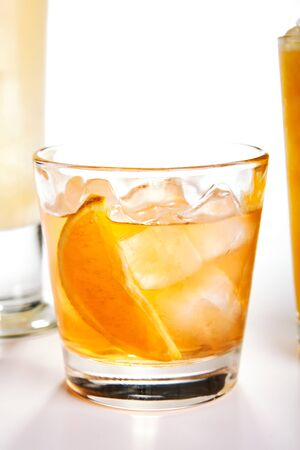 Fresh cocktail with orange and ice. White background. Imagens