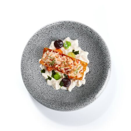 Crab and creamy cheese top view. Delicious chopped seafood and greenery on plate. Prepared dish with sauce. Tasty restaurant delicacy. Culinary composition, food presentation. Haute cuisine