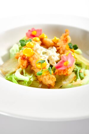 Warm salad with crispy langoustines. Delicious served dish with roasted seafood. Tasty food in white plate decorated with flowers and sauce. Haute cuisine, sicilian recipe. Restaurant menu Banque d'images