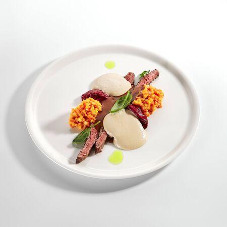 Canard sauce caroube et légumes. Viande rôtie servie avec risotto de carottes et citrouille dans une assiette. Cuisine gastronomique, gastronomie. Portion de nourriture de restaurant, plat principal cuit