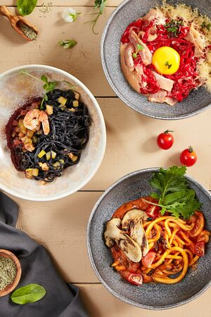 Noodles in ceramic bowls top view. Cooked flour products with sauces, spaghetti with meat, seafood and vegetables. Served pasta, restaurant meals on wooden table, rustic style serving Stockfoto