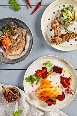 Hot meals in ceramic plates top view. European cuisine food, meat and seafood with vegetables. Appetizing delicatessens, gastronomy, served restaurant dishes and flavoring on wooden table