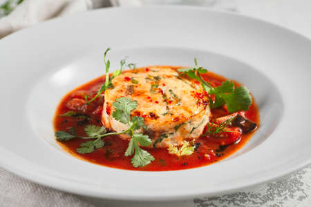 Salmon fish cake with tomato sauce and fresh greens. White bowl on rustic table with cloth. Gourmet food concept
