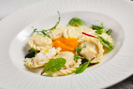 Cheese Pierogis with Cream of Pumpkin. Cottage cheese stuffing. Traditional Polish Dinner. Bright background. Stock fotó