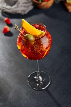 Classic aperol spritz cocktail. Spritz cocktail on dark background. Fresh orange drink. Festive christmas background.