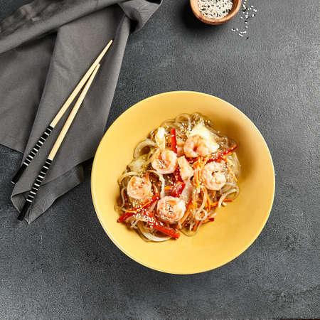 Asian Stir Fried Shrimp and Rice Noodles. Sesame Rice Noodles with Shrimp in yellow plate with wooden chopstick on dark slate table. Asian, authentic food concept. Zdjęcie Seryjne