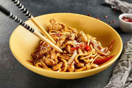 Hoisin chicken udon noodles. Yellow plate with wooden chopstick on dark slate table. Asian, authentic food concept.