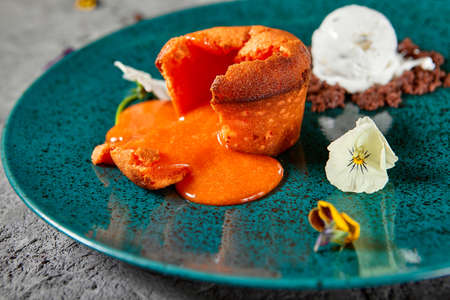 Carrot Fondant Cake with Ice Cream. Carrot Cake with liquid center served hot with ice cream. Dark green restaurant dish on textured gray table