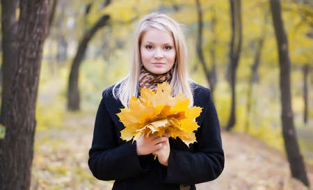 Autumn portrait of a girl with leaves in the hands Stock Photo - 8591339