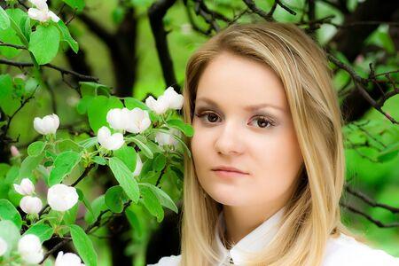 blonde girl near a flowering apple tree Stock Photo - 8591291