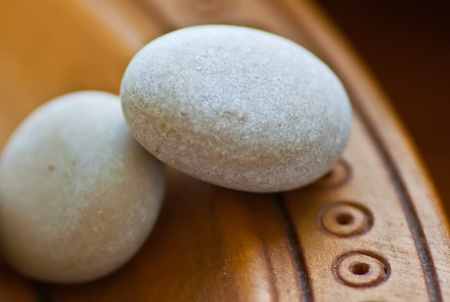 Two small white stones on a wooden plate photo