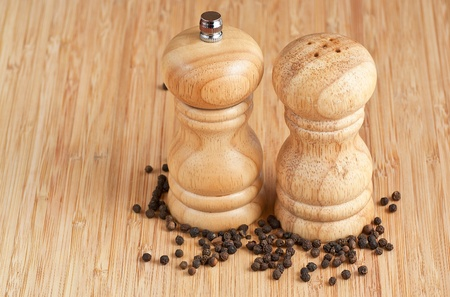 pepper grinder: salt and pepper grinders on a table, with pepper spread around