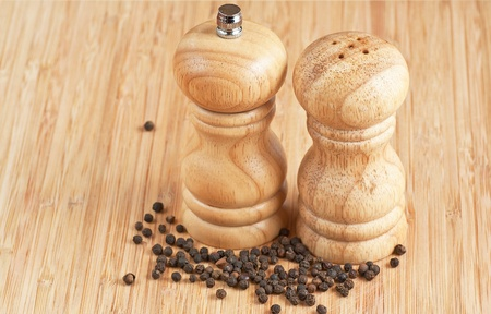 salt and pepper grinders on a table, with pepper spread around photo