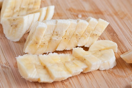 Freshly sliced bananas on a wooden board photo