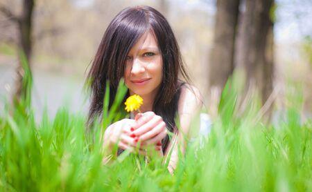 girl on yellow dandelion on green field photo