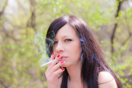 closeup of a pretty woman smoking at the street Stock Photo
