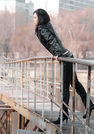 girl on an iron bridge looks in the frame Stock Photo - 10129577