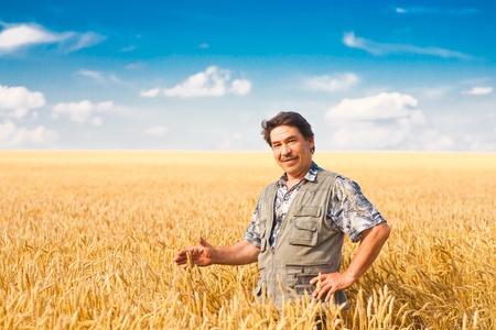農家: 農夫は小麦畑に立って、作物を見て 写真素材