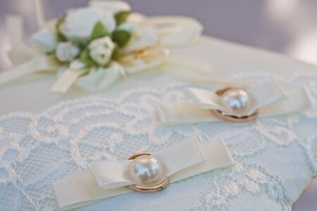 Closeup of golden wedding rings on white rose, DOF focus on diamonds photo
